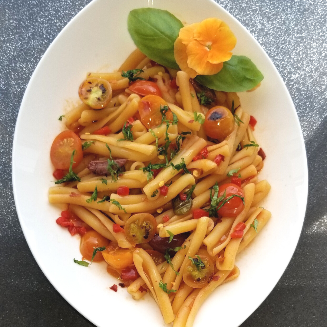 Spicy Casarecce with assorted cherry tomatoes, olives, basil and Nasturtium